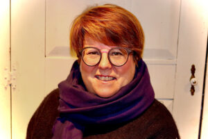Woman with glasses and purple scarf smiling