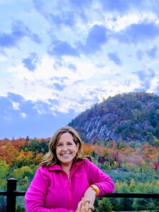 Woman in pink jacket posing in front of autumnal nature background