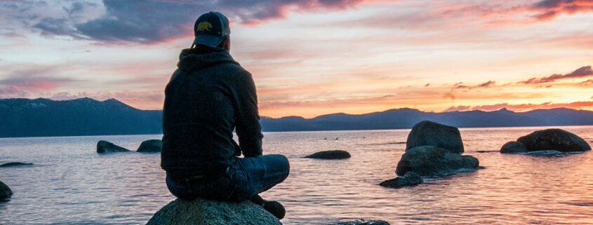 Silhouette of person sitting on rock looking out at sunset over water